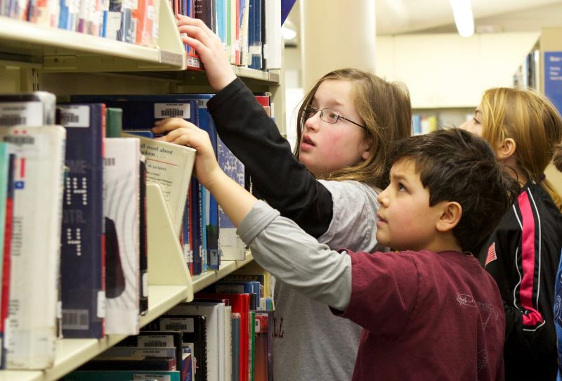 Students reaching for books on a library shelf at Foote School