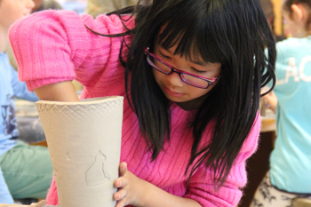 A student creating a ceramic art piece during art class