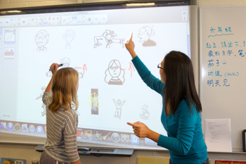 A teacher working with a student on a smart board in a classroom