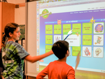 Two students working on a smart board in a classroom