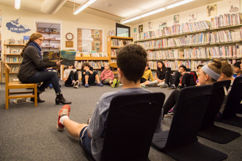 A teacher reading to a group of students sitting on the floor of a library