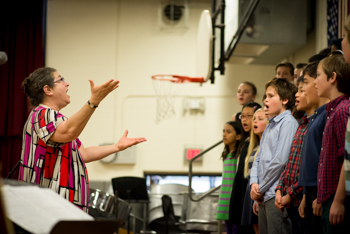 An instructor leading a choir of students in a gymnasium