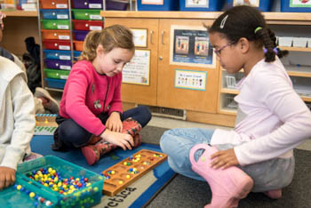 Two kindergarten girls playing a game on the floor of a classroom