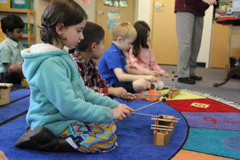 Kindergartens students playing instruments on the floor of a classroom