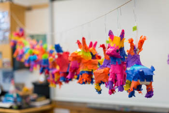 A row of pinatas hanging in a classroom