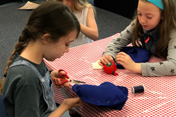 Students working together to hand-sew a French beret