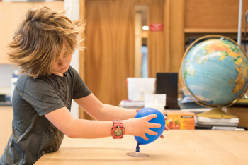 A student creating a model of the Earth in a science classroom