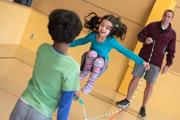 A teacher and students jumping rope during a physical education class