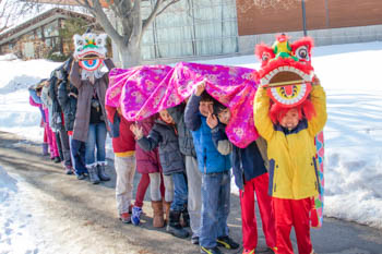 A line of students holding up a Chinese dragon