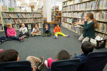 A librarian sitting with a group of students next to a wall of books