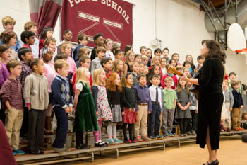 A choir instructor and a group of students singing in a gymnasium