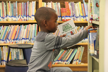 A student reaching for books from the shelf of a library