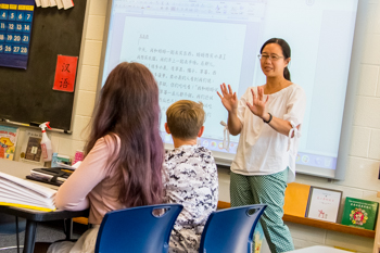 A teacher presenting to two students in a Chinese language class
