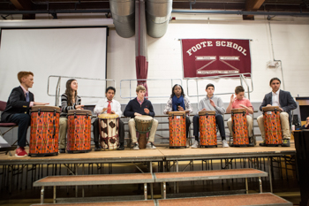A group of students playing drums on a stage