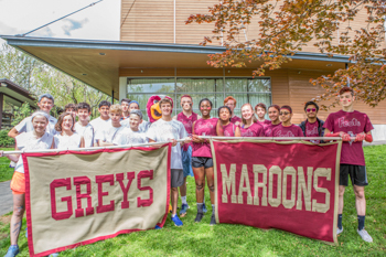 "Two groups of students holding banners that read ""GREYS"" and ""MAROONS"""