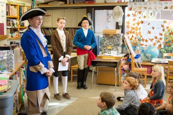 Students dressed in colonial American attire presenting to younger students