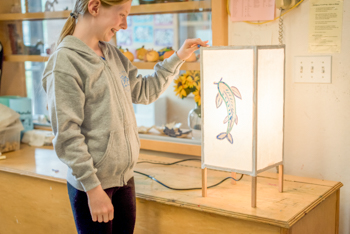 A student standing next to a light box project in an art class