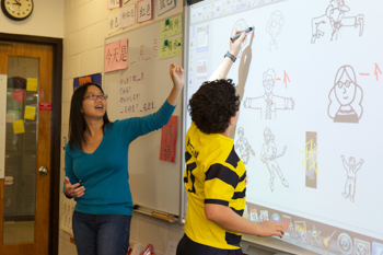 Students working on a smart board in a classroom
