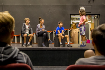Students acting on a stage during a drama class