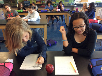Two students taking notes at a science lab table in a classroom