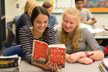 Two students reading Lord of the Flies together in a classroom