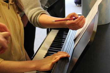 Students at a piano and one marking the music sheet