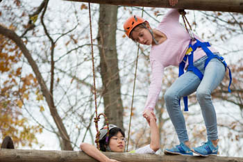 Students climbing and walking on a ropes course during a physical education class