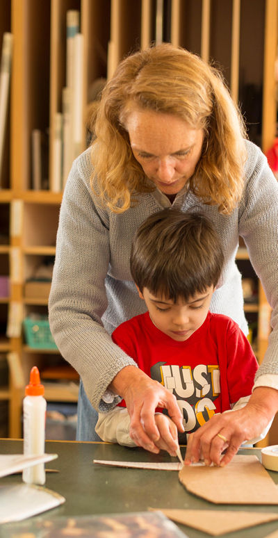A teacher helping a young student with a craft in a classroom